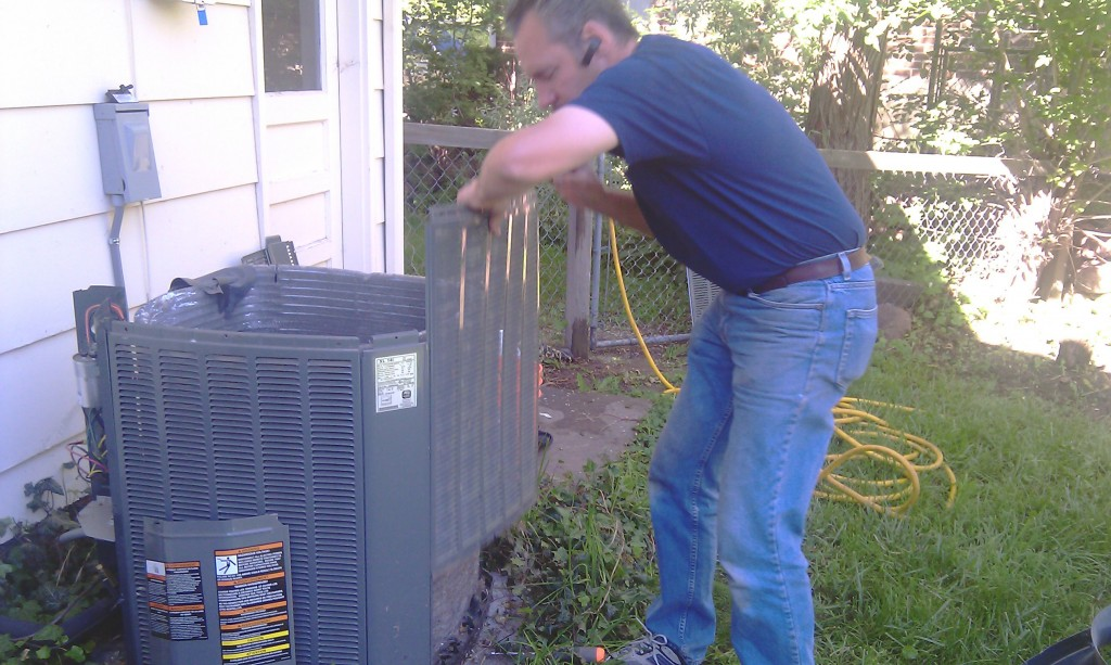 Karl cleans and checks the outside AC unit